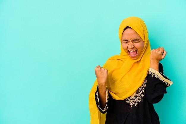 勝利、勝者の概念の後に拳を上げる青い背景で隔離の若いイスラム教徒の女性。