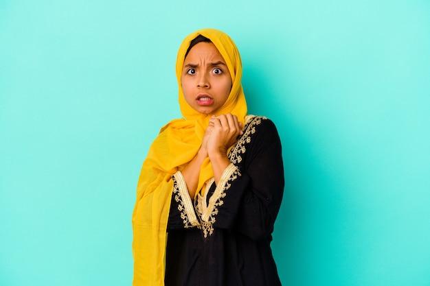 青い背景に孤立した若いイスラム教徒の女性は怖くて恐れています。