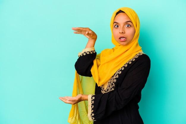 青い背景に孤立した若いイスラム教徒の女性は、手の間にコピースペースを持ってショックを受け、驚いています。