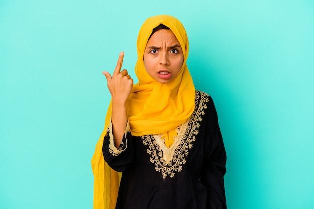 人差し指で失望のジェスチャーを示す青い背景で隔離の若いイスラム教徒の女性。