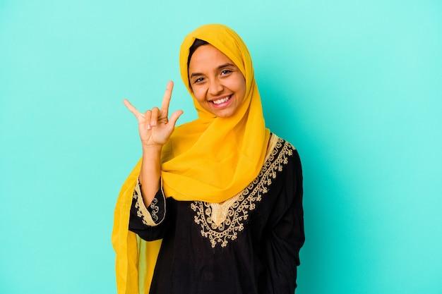 革命の概念として角のジェスチャーを示す青い背景に分離された若いイスラム教徒の女性。