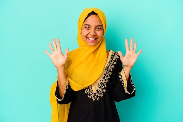 青の背景に分離された若いイスラム教徒の女性は、手で10番を示しています。