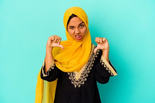 親指を下に表示し、嫌悪感を表現する青い背景に分離された若いイスラム教徒の女性。