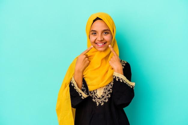 입에서 손가락을 가리키는 파란색 배경 미소에 고립 된 젊은 무슬림 여성.