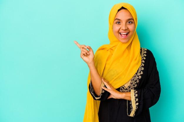 青い背景に孤立した若いイスラム教徒の女性は、人差し指を離れて元気に指して微笑んでいます。