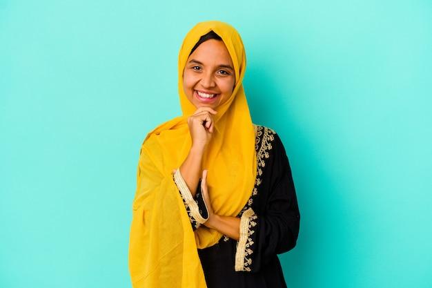 青の背景に分離された若いイスラム教徒の女性は、幸せと自信を持って笑顔、手で顎に触れます。