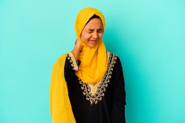 座りがちな生活のために首の痛みに苦しんでいる青い背景で隔離の若いイスラム教徒の女性。