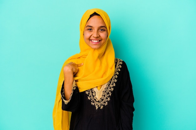 Молодая мусульманка изолирована на синей стене человека, указывая рукой на пространство для копирования рубашки, гордая и уверенная в себе