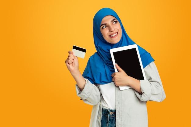 黄色の若いイスラム教徒の女性。スタイリッシュでトレンディで美しい女性モデル