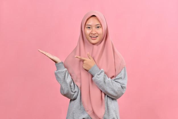 분홍색 배경에서 포즈를 취한 젊은 이슬람 여성은 손바닥에 복사 공간을 들고 흥분했습니다.