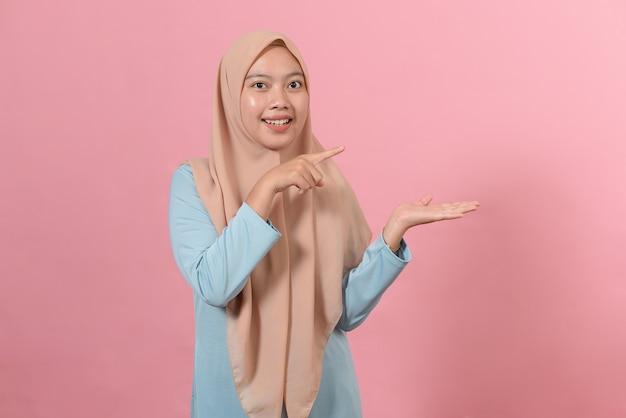 분홍색 배경에서 포즈를 취한 젊은 이슬람 여성은 손바닥에 복사 공간을 들고 흥분했습니다