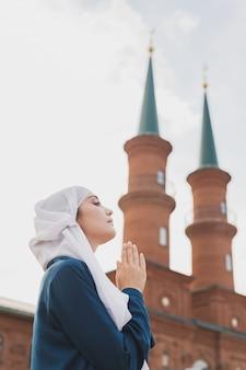 Молодая мусульманка в молитве носить хиджаб поститься молиться аллаху на фоне мечети