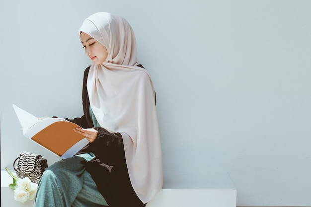 Young muslim woman reading a book
