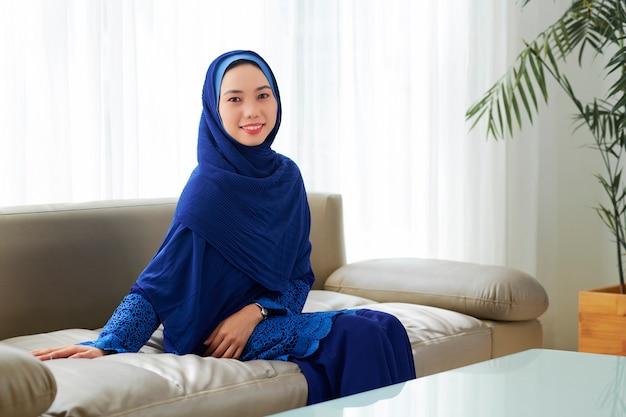 ソファーで休んで若いイスラム教徒の女性