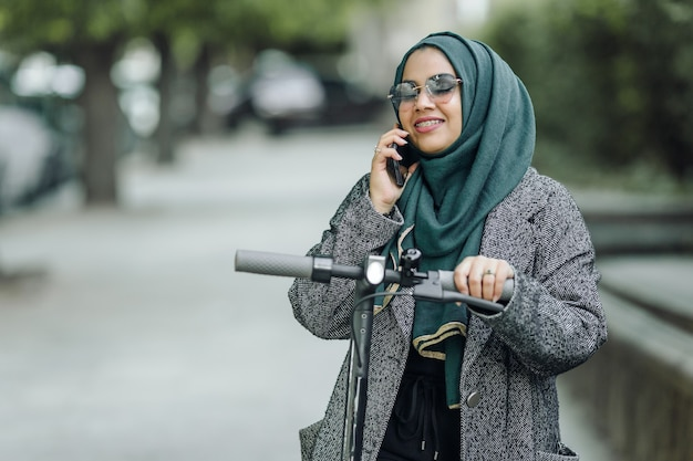 Young muslim woman riding a scooter on a street