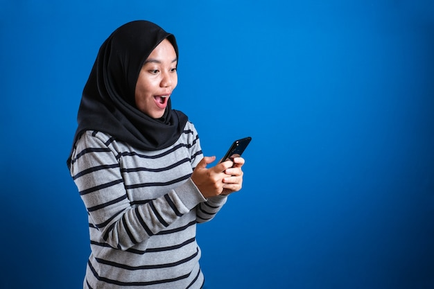 Young muslim woman shocked expression, looking at her phone against blue backgound