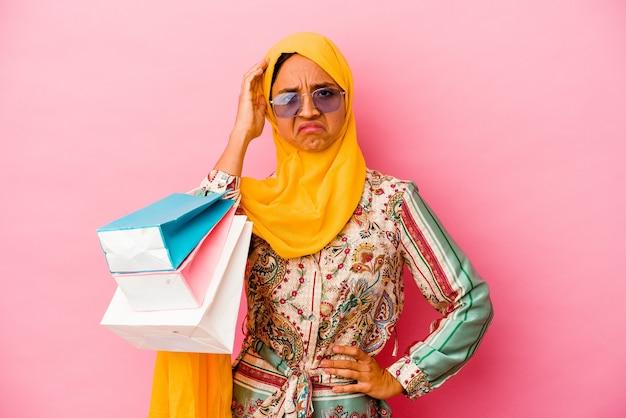 Молодая мусульманка, делающая покупки одежды, изолированные на розовом фоне, в шоке, она вспомнила важную встречу.