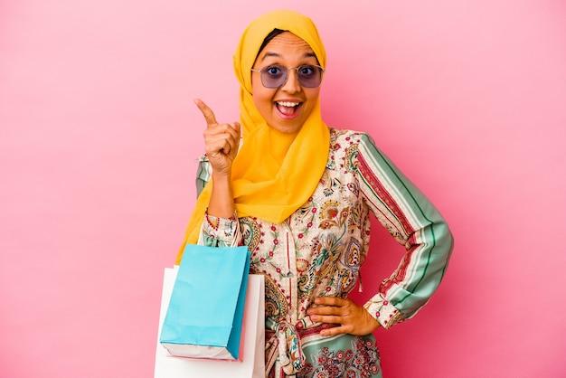 アイデア、インスピレーションのコンセプトを持つピンクの背景に分離されたいくつかの服を買い物する若いイスラム教徒の女性。
