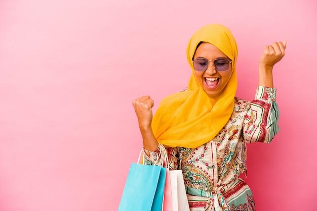 Молодая мусульманская женщина, делающая покупки в одежде, изолированной на розовом фоне, поднимая кулак после победы, концепции победителя.