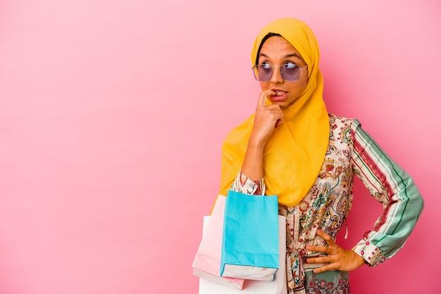 Молодая мусульманская женщина, делающая покупки в одежде, изолированной на розовом фоне, расслабилась, думая о чем-то, глядя на копию пространства.