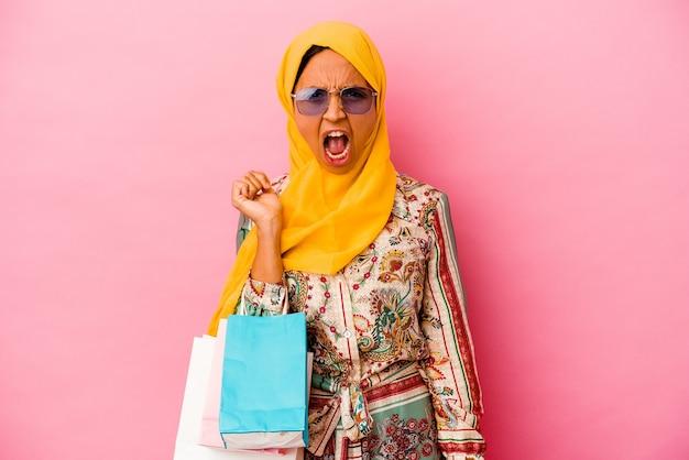 Молодая мусульманская женщина, делающая покупки в одежде, изолирована на розовом фоне, кричала очень сердито и агрессивно.