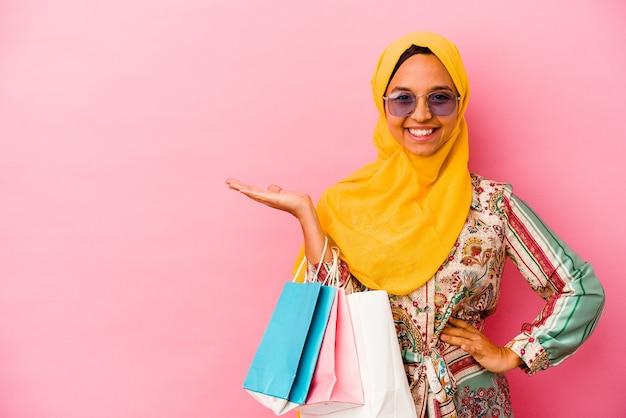 Молодая мусульманская женщина делает покупки в одежде, изолированной на розовом фоне, показывая пространство для копии на ладони и держа другую руку на талии.