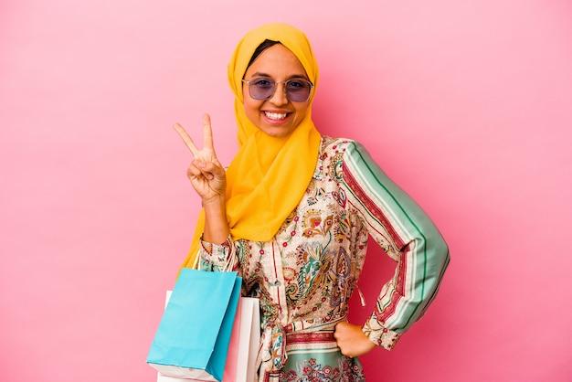 Молодая мусульманская женщина, делающая покупки в одежде, изолированной на розовом фоне, показывая номер два пальцами.