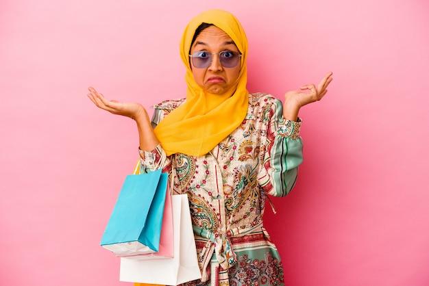 Молодая мусульманская женщина, делающая покупки одежды, изолированные на розовом фоне, пожимает плечами и смущает открытые глаза.