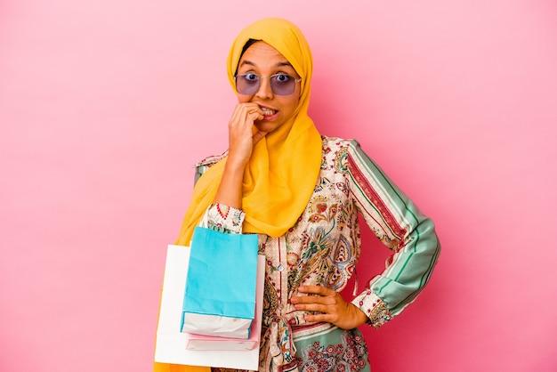 손톱, 긴장 하 고 매우 불안을 물고 분홍색 벽에 고립 된 일부 옷을 쇼핑하는 젊은 무슬림 여성.