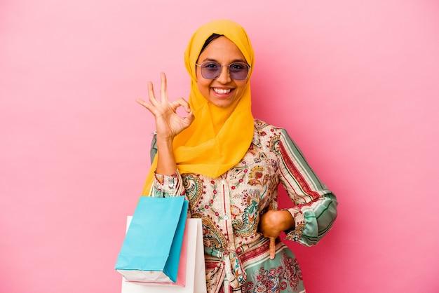 Молодая мусульманская женщина, делающая покупки в какой-то одежде, изолированной на розовой стене, веселая и уверенная, показывая одобренный жест.