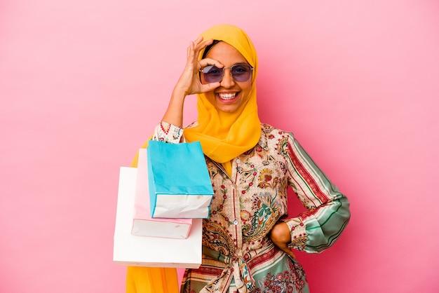 Молодая мусульманская женщина, делающая покупки в какой-то одежде, изолированной на розовой стене, взволнована, держа на глазах одобренный жест.