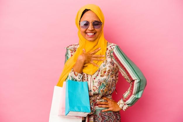 Молодая мусульманка, делающая покупки какой-то одежды, изолированной на розовой стене, громко смеется, держа руку на груди.