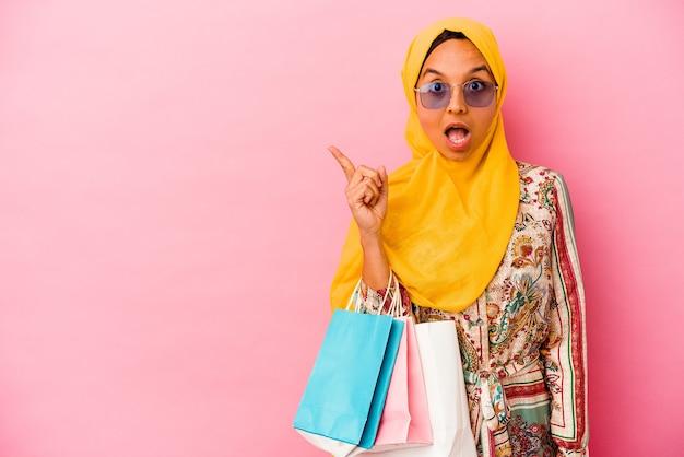 Молодая мусульманская женщина делает покупки в одежде, изолированной на розовой стене, указывая в сторону