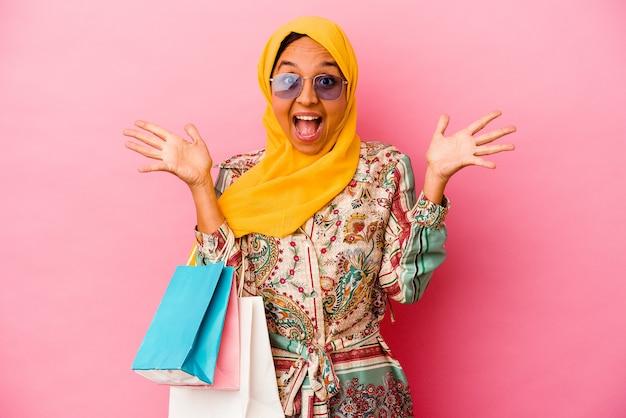 Молодая мусульманская женщина делает покупки в одежде, изолированной на розовой стене, получая приятный сюрприз, взволнованный и поднимающий руки.