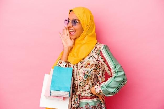 Молодая мусульманская женщина делает покупки в одежде, изолированной на розовой стене, кричит и держит ладонь возле открытого рта.