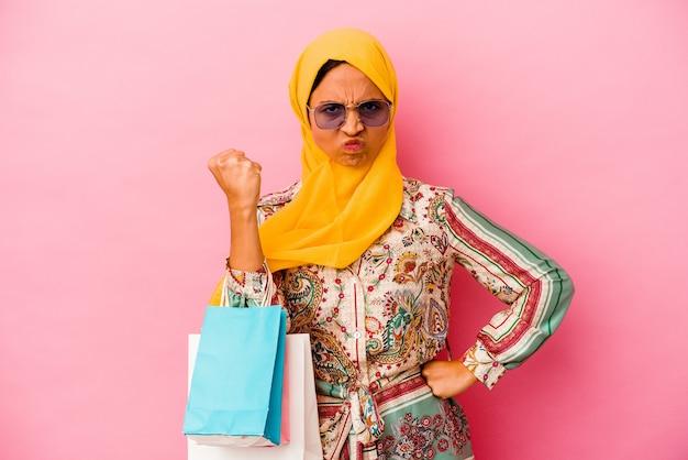 카메라, 공격적인 표정에 주먹을 보여주는 분홍색 벽에 고립 된 몇 가지 옷을 쇼핑하는 젊은 무슬림 여성.