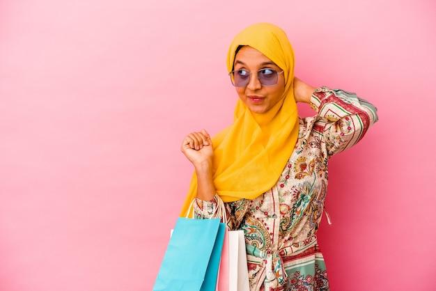 Молодая мусульманка делает покупки в одежде, изолированной на розовой стене, касаясь затылка, думая и делая выбор.