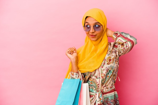 Young muslim woman shopping some clothes isolated on pink wall touching back of head, thinking and making a choice.