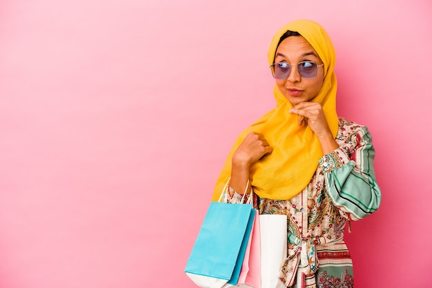Young muslim woman shopping some clothes on pink looking sideways with doubtful and skeptical expression.