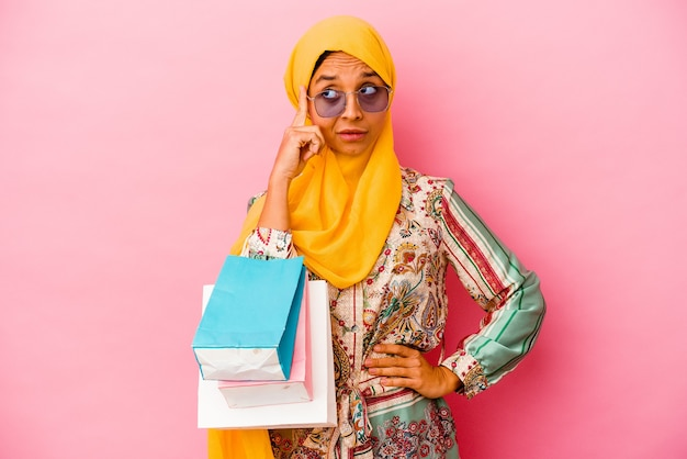 Young muslim woman shopping some clothes on pink pointing temple with finger, thinking, focused on a task.
