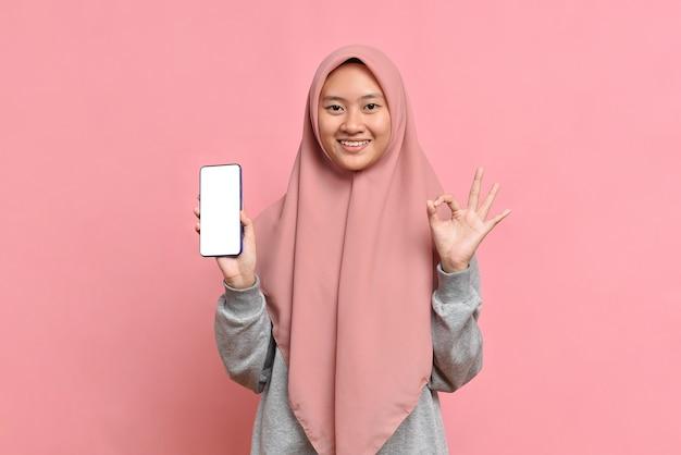 분홍색 배경에 ok 표시가 있는 전화 화면 디스플레이를 보여주는 젊은 이슬람 여성