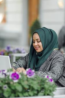 通りのカフェに座って、ラップトップで見ている若いイスラム教徒の女性