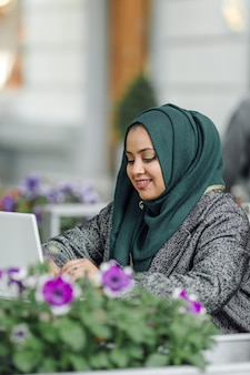 Young muslim woman sitting in a street cafe and looking in a laptop