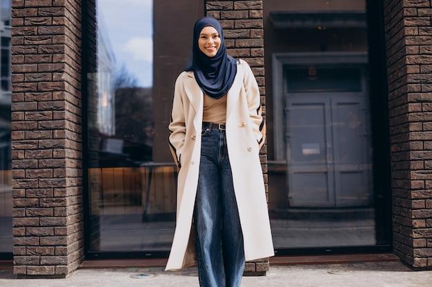 거리에서 걷는 젊은 무슬림 여성 학생