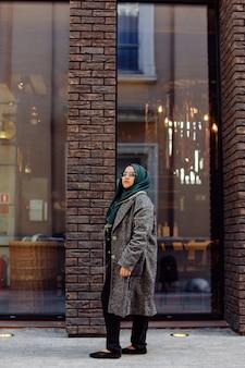 거리에서 사진을 찍는 젊은 이슬람 여성