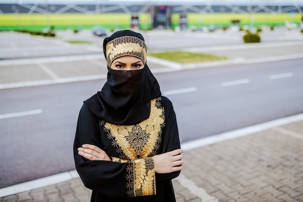 Young muslim woman in traditional wear standing outdoors with arms crossed.
