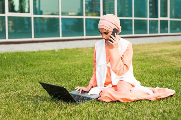 Молодая мусульманская женщина с помощью мобильного телефона и ноутбука в парке