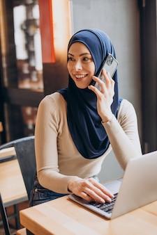 전화를 사용하고 카페에서 컴퓨터에서 작업하는 젊은 무슬림 여성