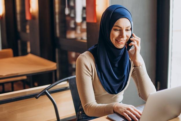 Молодая мусульманская женщина с помощью телефона и работает на компьютере в кафе
