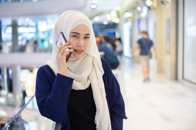 Young muslim woman using phone in supermarket.